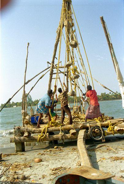 Filets chinois. Les pêcheurs relèvent le filet en descendant le mat servant de levier. Des pierres servent de contre-poids
